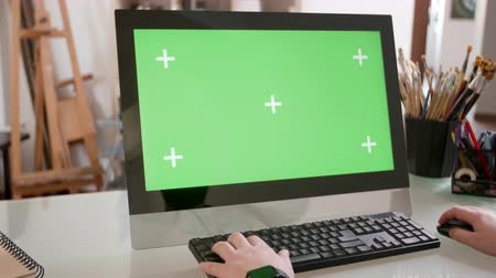 コンピュータモニター : Male hands typing a text on the keyboard in front of a green screen. Young painter works on his computer in a creative workshop.