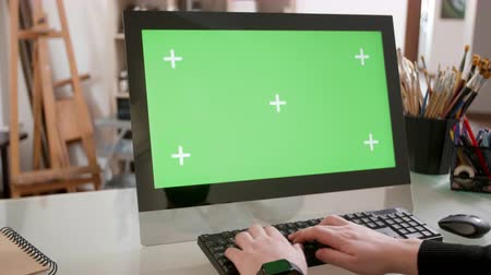 artsy : Creative designer working at his computer with green screen on the display. Artistic workshop ambiance. Chroma key. Stock Footage