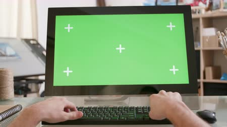 artsy : Male hands typing on a keyboard in front of a green screen. Artistic workshop environment. Designer working on new ideas.