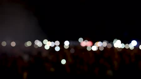 night life : People at a rock concert with their flashlights on and hands up in the air. Sea of lights at a music concert.