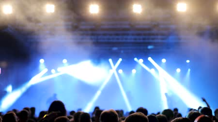 rock festival : Fans watch their favorite music band performing on the stage. Bright lights on their heads. Shot from behind a crowd.