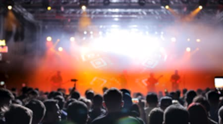 scena : Beautiful warm lights in the background of a rock band performing on the stage. Crowd cheering and enjoying favorite band.