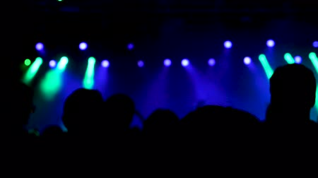 many lights : Slow motion shot from behind tof crowd at a music event. Beautiful strobe lights in the background. Stock Footage