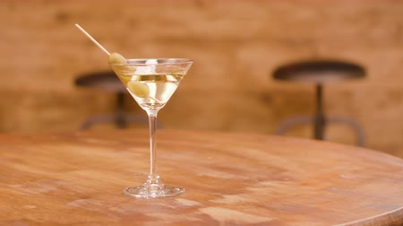 liquid : A glass of martini with olives on a wooden table