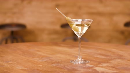 vermouth : Parallax shot of a martini glass on an empty wooden table Stock Footage