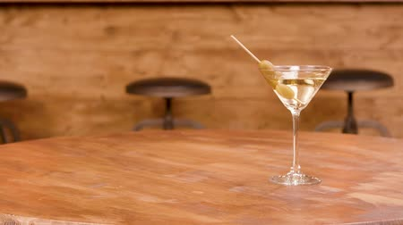 vermouth : Sliding towards a glass of martini on an empty wooden table