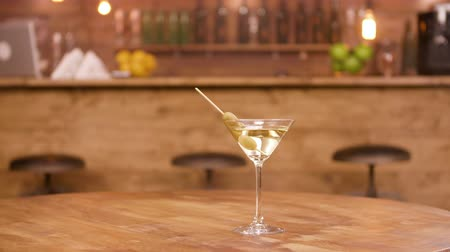 vermouth : Parallax shot of a martini glass on an empty wooden table with bar counter on the background