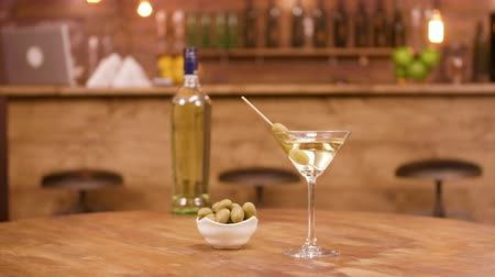 vermouth : A bottle and a glass of martini with olives on a wooden table