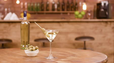 vermouth : Slider shot of a bottle and a glass of martini with olives on a wooden table