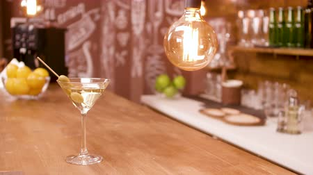 vermouth : A glass of martini on a bar counter in an empty restaurant interior