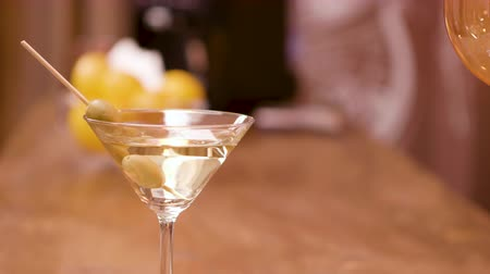 martini glasses : Green olives in a glass of martini on a bar counter