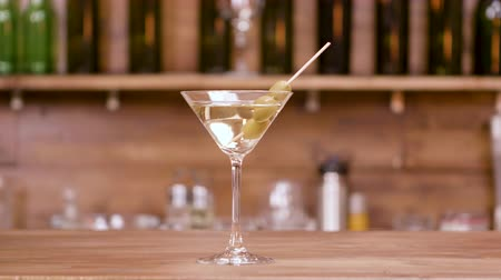 vermouth : Glass of alcoholic beverage on a bar counter. Martini glass garnished with green olives.