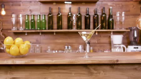 vermouth : Slider shot of a glass of martini beverage on a bar background. A glass of martini with green olives on a bar counter.