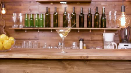 vermouth : Parallax shot of a glass of martini beverage on a bar background. A glass of martini with green olives on a bar counter.