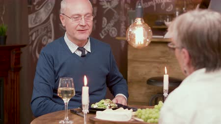 juntar : Old man making a proposal to his partner on a romantic dinner. Old couple decides to get married on a date. Vídeos