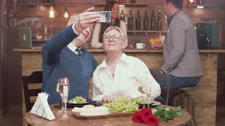 ailelerin : Beautiful old couple on a date taking a selfie in a fancy restaurant. Elderly couple using new technology