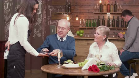 cüzdan : Old people in a restaurant using new technology to pay the bill. Using NFC to make a payment in a restaurant.