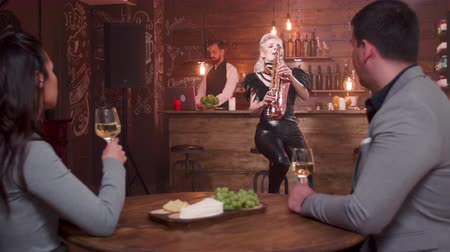 saxofone : Young couple listening to a live saxophone performance. Couple of young people on a date admiring a beautiful female saxophonist. Stock Footage