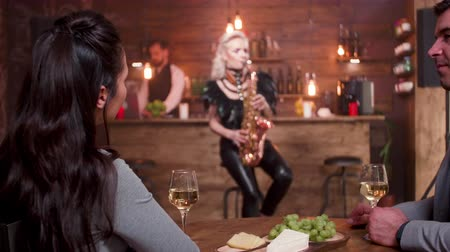 saxofonist : Man and woman on a romantic date listening to a live jazz concert. Performing a jazz song on a saxophone for a small audience.