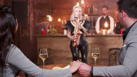 saxofone : Beautiful couple hold hands and listen to a live saxophone performance. Young love birds on a romantic date.