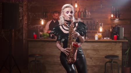 saxofon : Young woman passionately playing a romantic song on a saxophone in front of a bar counter. Romantic atmosphere in a local pub. Dostupné videozáznamy