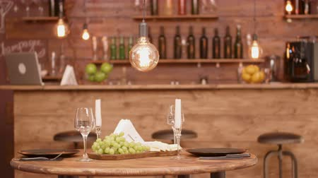 winogrona : A wooden round table in an empty restaurant with cheese and grape appetizer. Empty restaurant before a date. Wideo
