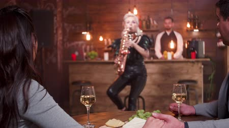 saxofone : Man holds the hand of his fiancee while a female saxophonist plays passionately. Couple on a romantic date. Stock Footage