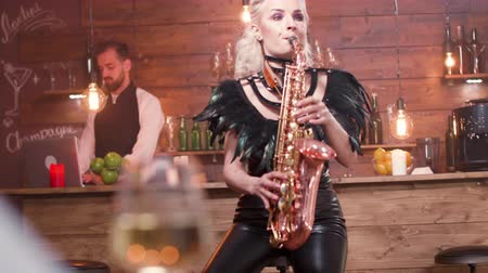 saxofonist : Female saxophonist performing a song in front of an audience. Solo blues concert in a vintage restaurant with romantic atmosphere. Stockvideo