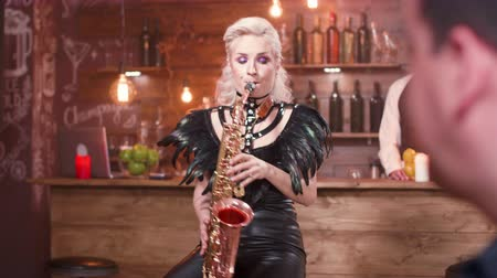 saxofone : Over the shoulder shot of a man listening to a live saxophone performance. Woman performing a song on a saxophone on a private party. Stock Footage
