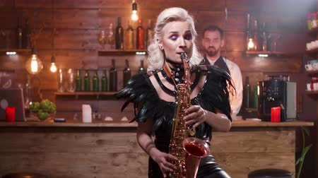 saxofon : Pretty woman in black stage costume playing a melody on saxophone
