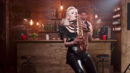 saxofon : Young blonde female musician performs a song on her saxophone sitting on a high bar chair Dostupné videozáznamy
