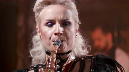 saxofon : Female musician plays a song on a saxophone