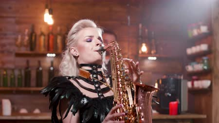 sassofono : Woman in a dark leather costume performs a song on a saxophone
