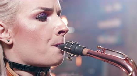 saxofonist : Extreme close-up portrait of a female musician performing a song on a saxophone Stockvideo