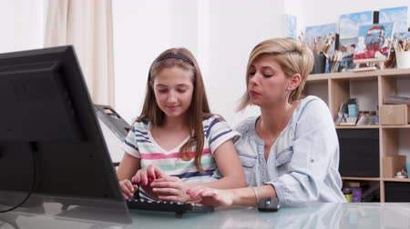 role model : Young attractive woman helping a teenage girl with a text on computer. Mother helping her daughter to write a text.