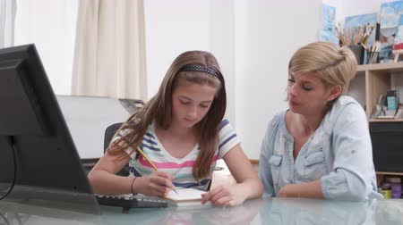 role model : Teenage girl drawing something in her notebook and her mother talks to her. Mom and her daughter at a desk.