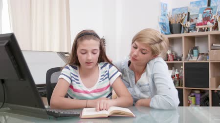role model : Loving mother and her teenage girl reading a book together. Parent and her kid reading a story from a book. Stock Footage