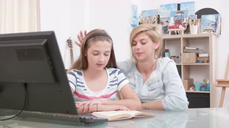 role model : Teenage girl reading to her mom from a book. Young daughter practicing her reading skills while her mom listens. Stock Footage