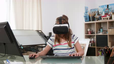 fejhallgató : Teenage girl using a mouse a keyboard and a vr headset to play a game. Teen flying a spaceship virtually. Stock mozgókép