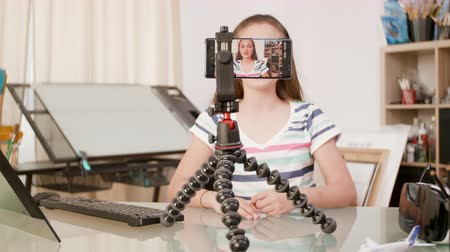 speaking : Smartphone on a tripod filming a young girl talking. Teenage girl dreams to become a famous vlogger. Stock Footage