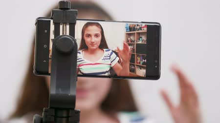 получать : Teenage girl filming herself on a smartphone. Making a video for her channel to get more followers.