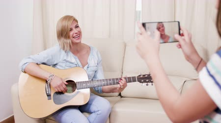 подростковый возраст : Daughter making a video with her mother playin on an acoustic guitar. Making an amateur music video. Стоковые видеозаписи