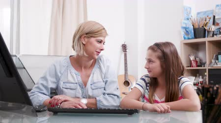 role model : Young beautiful woman looks at her daughter and smiles at her. Female parent and teenage daughter bonding.