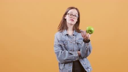promover : Teenage girl hold an apple in her hand and promotes healthy eating. Beautiful teen isolated over yellow background. Stock Footage