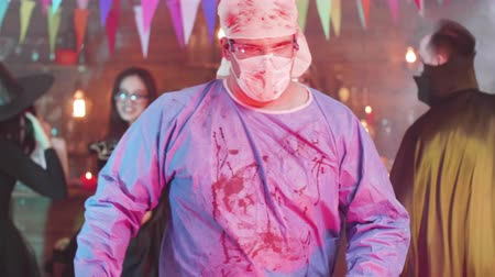 psycho : Slow motion shot of a man in psycho mad surgeon costume at a halloween party. He turns to the camera and looks scary all stained in blood. Stock Footage