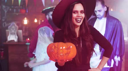 disfarçar : Young woman in a witch costumes make a evil laugh holding a carved pumpkun