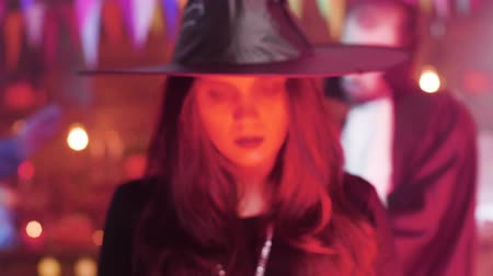 disfarçar : Woman in witch costume with a evil look at a halloween party Vídeos