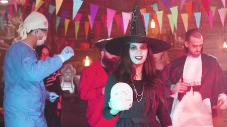 disguise : Young woman disguised in witch costume hold a skull in her hands at a halloween party