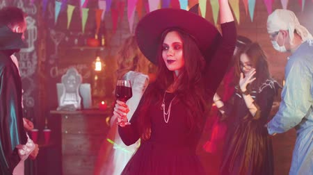 disguise : Attractive woman disguised as a witch dances with a glass of blood at a halloween party
