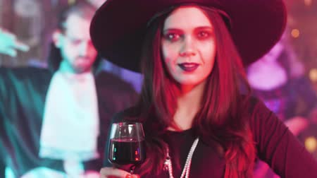 witch hat : Woman in witch costume with a beautiful smile and evil eyes at a halloween party Stock Footage